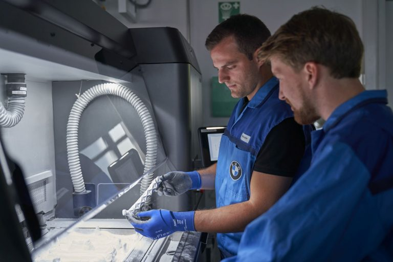 Removing powder material from 3d printed parts at BMW.
